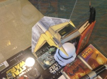 over head shot of a paper Naboo starfighter. This is the second paper ship that is being held up by human hair. Again, not mine. What little I had I roped himself a couple of sea turtles, lashed them together and made a raft.